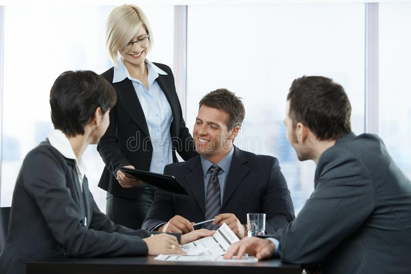Happy businesspeople at meeting. In office, standing assistant handing over contract to executive sitting with colleagues royalty free stock photos