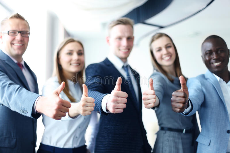 Happy businesspeople. Portrait of happy businesspeople standing in office showing thumb up royalty free stock photography