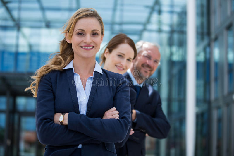 Happy businesspeople standing with their hands folded stock photo