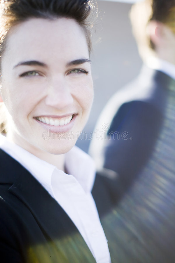 Happy businesswoman. Close view of attractive businesswoman standing wearing suit smiling with businessman standing next to her stock photos