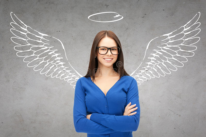 Happy businesswoman with angel wings and nimbus. Business, angel investor, safety, security and people concept - smiling young businesswoman with wings and royalty free stock image