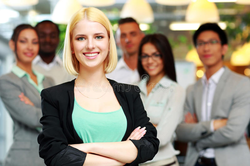 Happy businesswoman with arms folded. Standing in front her colleagues royalty free stock photo
