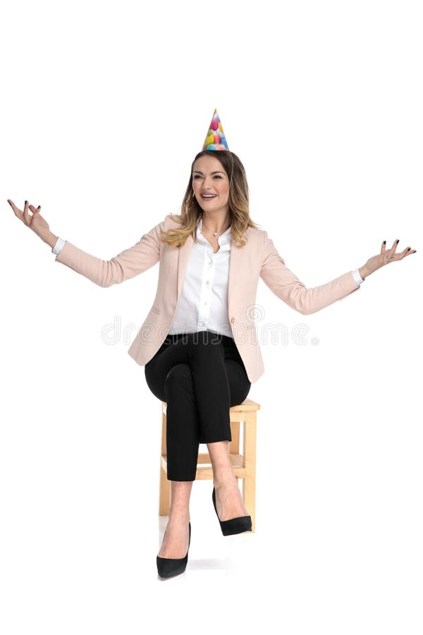 Happy businesswoman with birthday hat makes welcoming gesture. While sitting on wooden stool and looking up to side stock photos