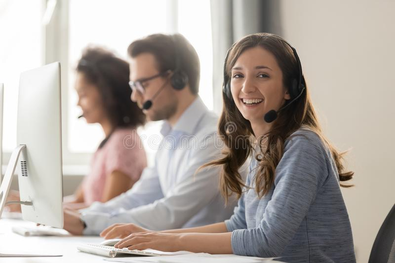 Happy businesswoman call center agent looking at camera at workplace royalty free stock photography