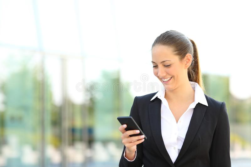 Happy businesswoman checking phone message in the street stock images