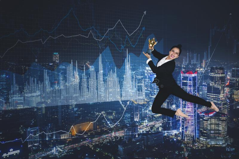 Happy businesswoman dances with trophy in the sky stock image
