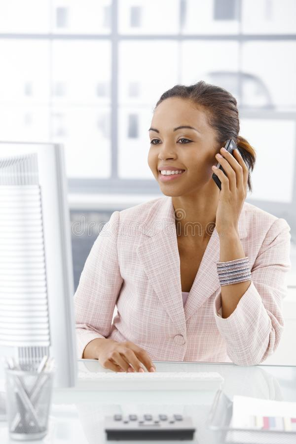Happy businesswoman at desk on call. Happy businesswoman sitting at desk, looking at screen, on mobile phone call stock photography