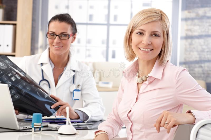 Happy businesswoman at doctor's medical office stock photography