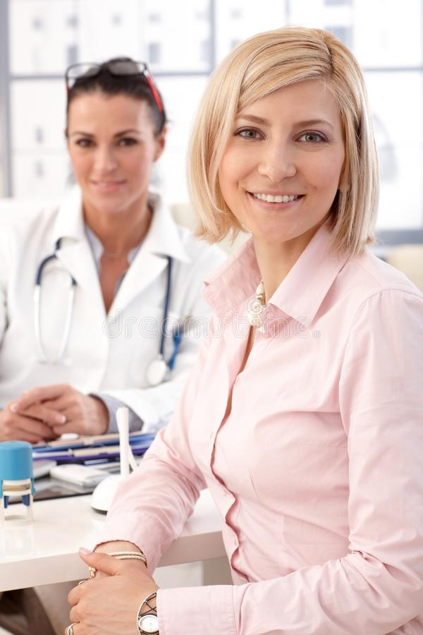 Happy businesswoman at doctor`s medical office. Close up of a happy blonde casual businesswoman at doctor`s medical office. Smiling and looking at camera royalty free stock photo