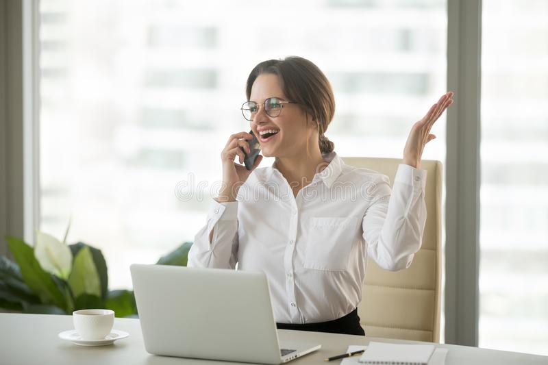 Happy businesswoman excited about hearing good news talking on p. Happy businesswoman excited about hearing good news talking on cell phone in office, smiling royalty free stock image