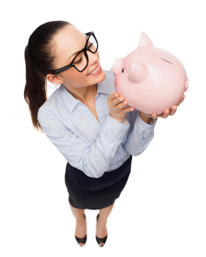 Happy businesswoman in eyeglasses with piggy bank stock photos