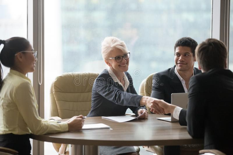 Happy businesswoman handshaking businessman over conference table at team meeting royalty free stock image