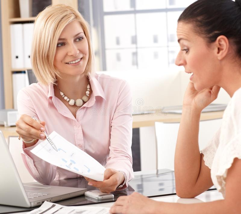 Happy businesswoman having a meeting at office. Happy blonde casual businesswoman having a work meeting at business office, with chart and pen in hand stock images