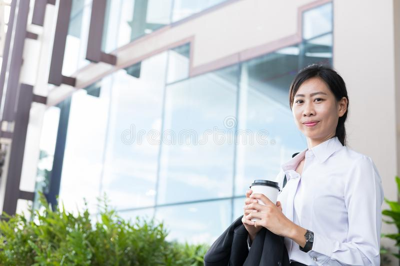 Businesswoman holding coffee outside office building. beautiful royalty free stock image