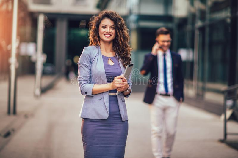 Happy businesswoman holding digital tablet outside of modern building, businessman in background. Young happy businesswoman holding digital tablet outside of stock photo