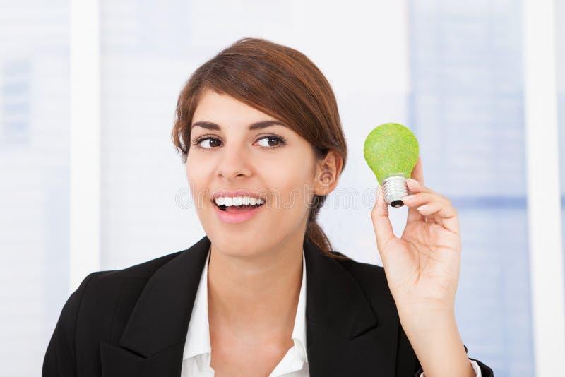 Happy businesswoman holding green light bulb royalty free stock photo