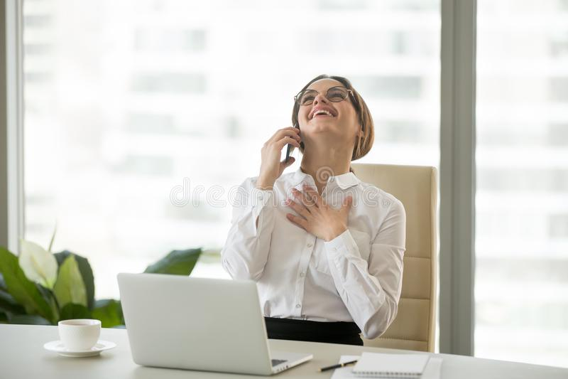 Happy businesswoman laughing while talking on mobile phone in of. Happy millennial businesswoman laughing having funny conversation talking on phone in office royalty free stock photos