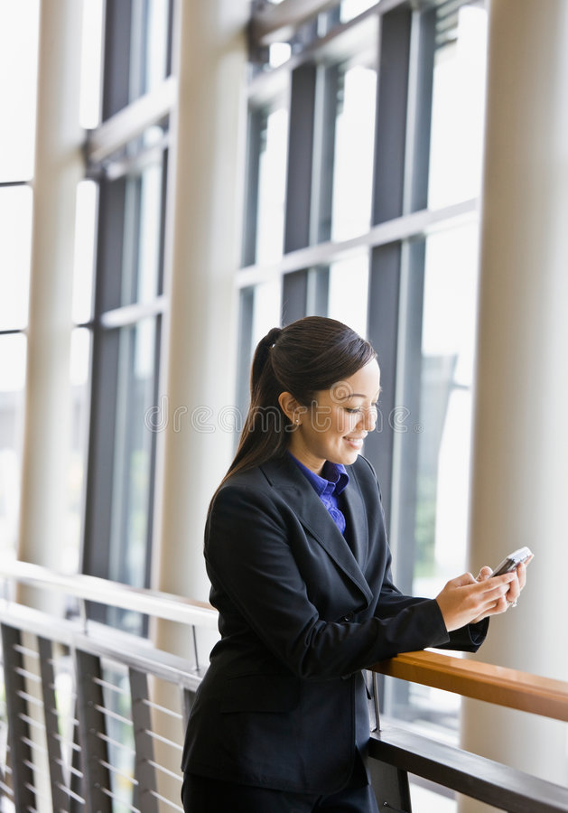 Happy businesswoman leaning on railing in office stock photo