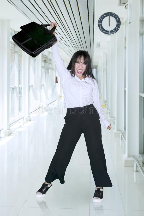 Happy businesswoman lifting a suitcase in corridor stock photos