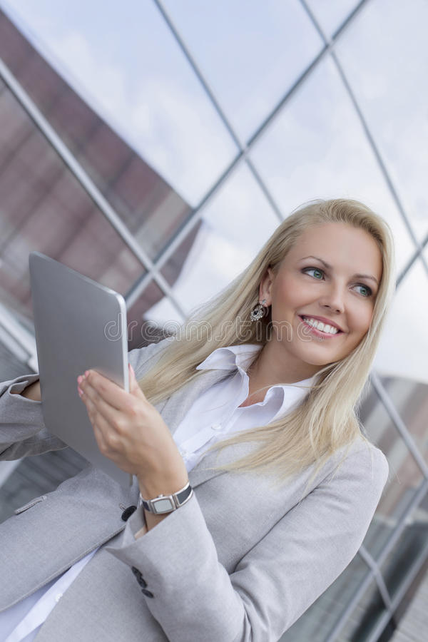 Happy businesswoman looking away while holding digital tablet against office building stock photo