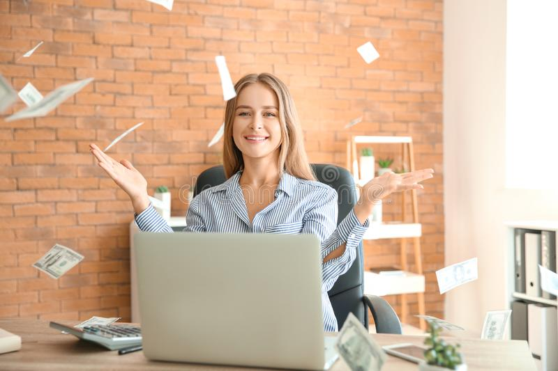 Happy businesswoman with lot of money in office stock photography