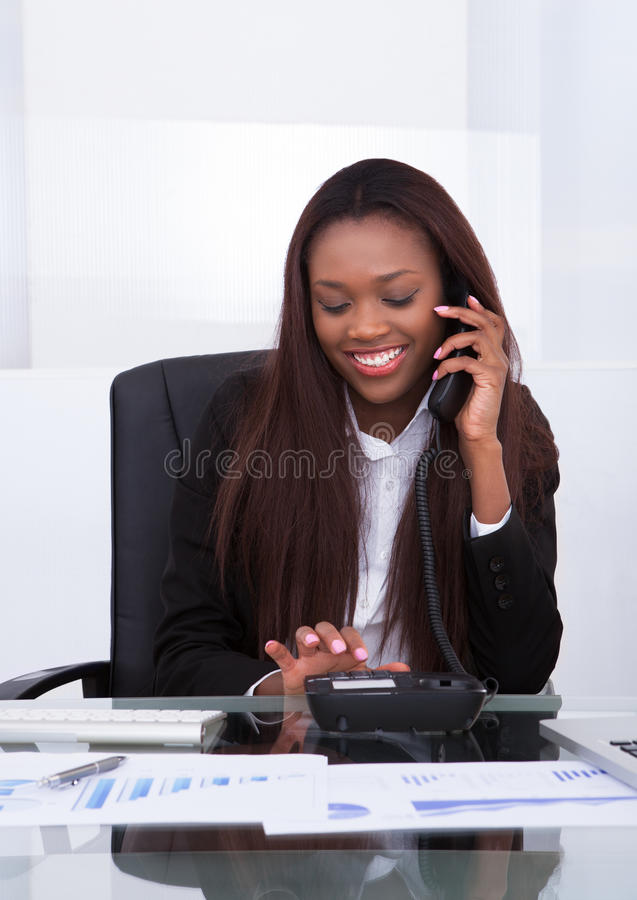 Happy businesswoman making a call from landline stock photography