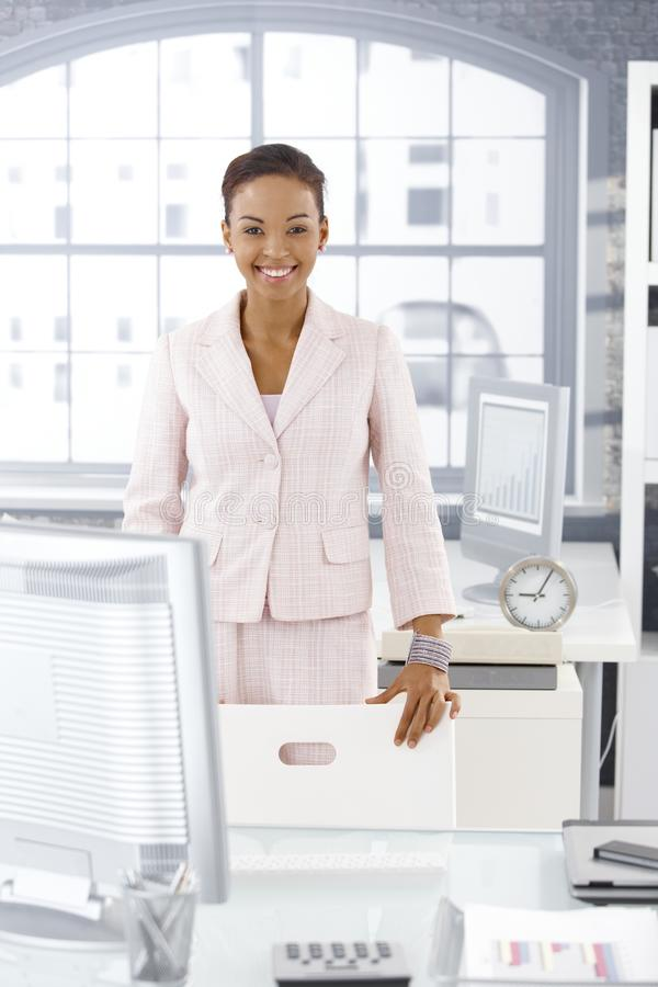 Happy businesswoman in office. Happy businesswoman standing at desk in bright office, smiling at camera stock photography