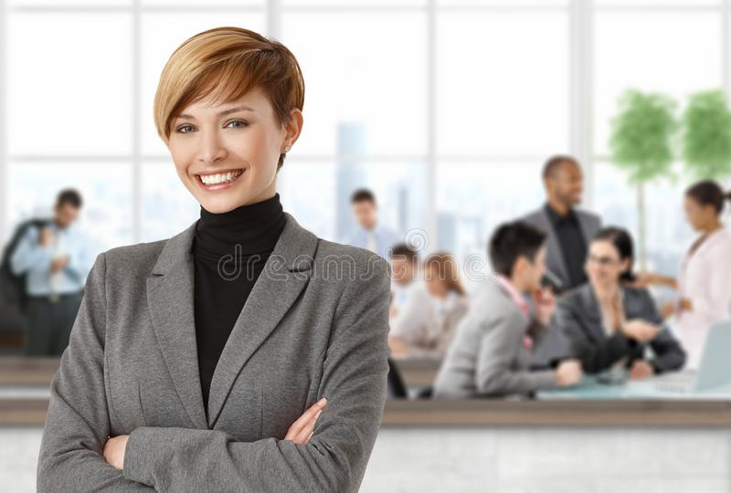 Happy businesswoman at office. People working in background royalty free stock photography