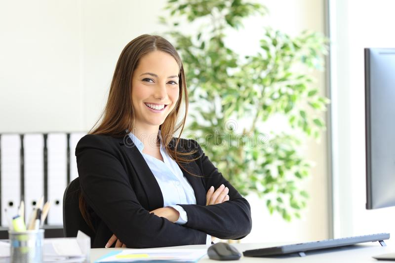 Happy businesswoman at office posing looking at you stock images