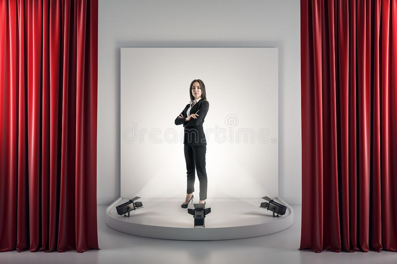 Happy businesswoman on pedestal. Best employee and leadership concept. Happy businesswoman standing on illuminated pedestal on concrete background with red royalty free stock photos