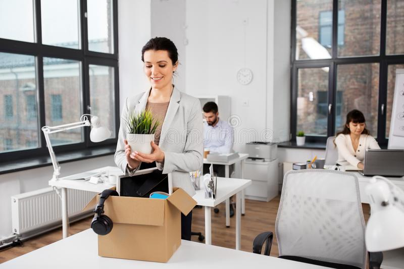 Happy businesswoman with personal stuff at office stock photography