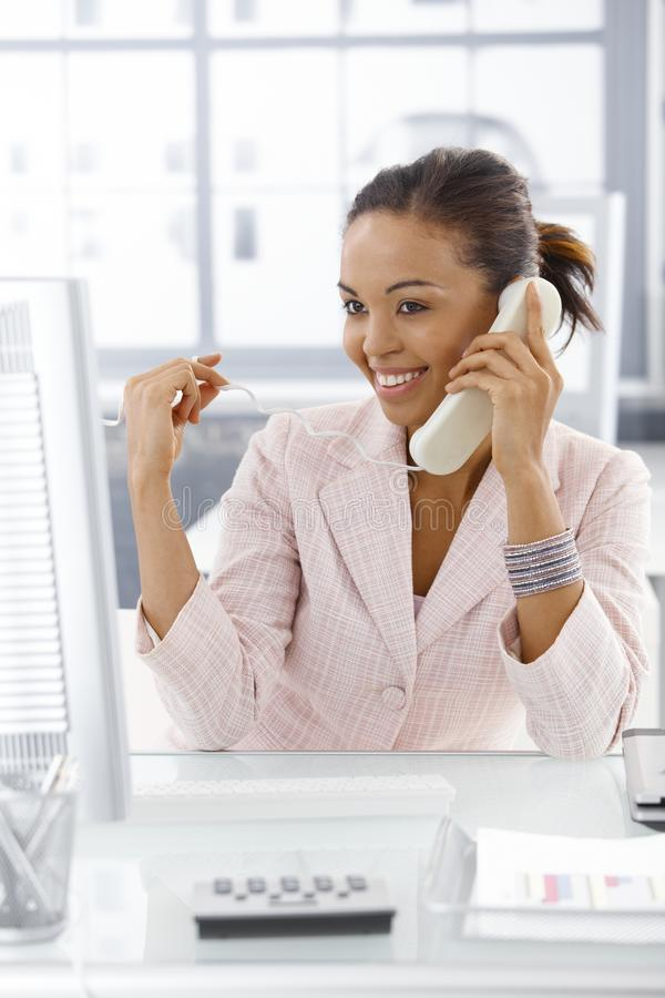 Happy businesswoman on phone call. Happy businesswoman sitting at desk, looking at screen, speaking on landline phone royalty free stock photo