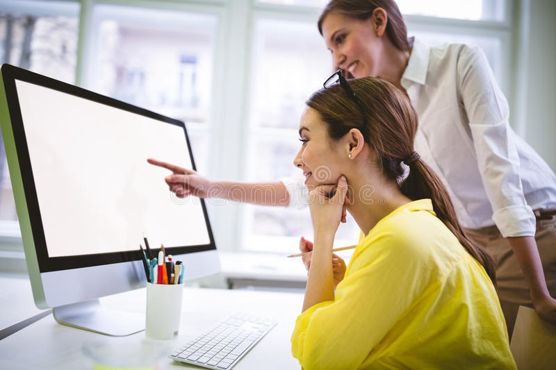 Happy businesswoman pointing at computer screen to colleague at creative office stock images