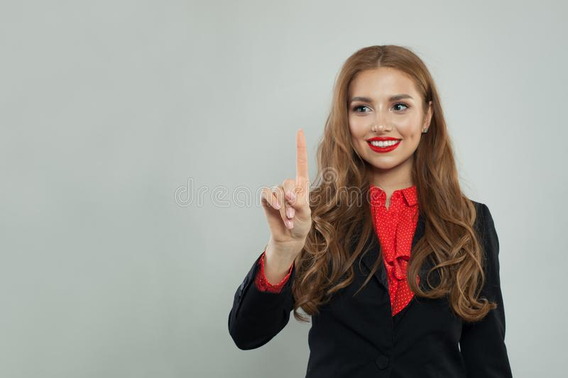 Happy businesswoman pointing her finger to empty copy space on gray banner background stock photography