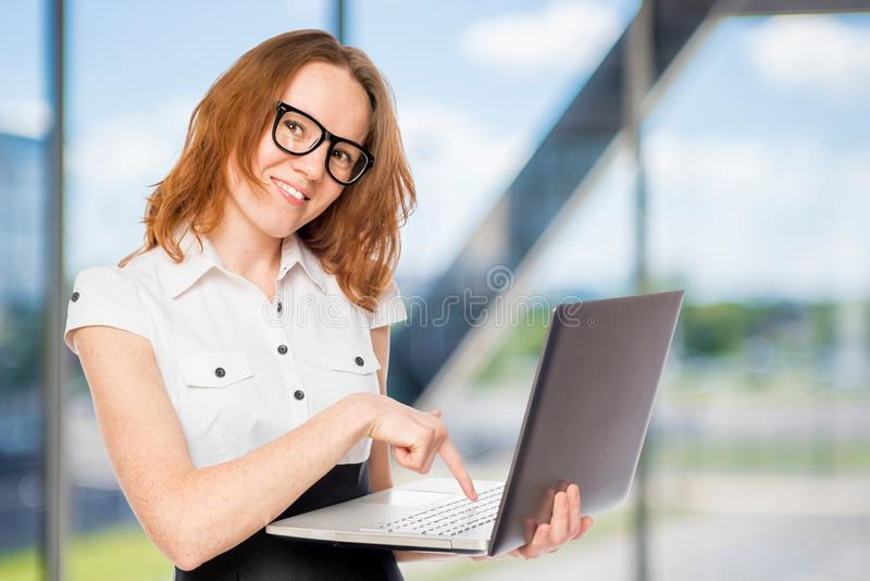 Happy businesswoman presses a button on the laptop royalty free stock image