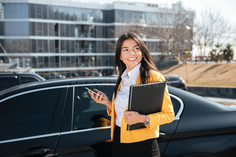 Happy businesswoman r standing near the car and using mobile phone stock photography
