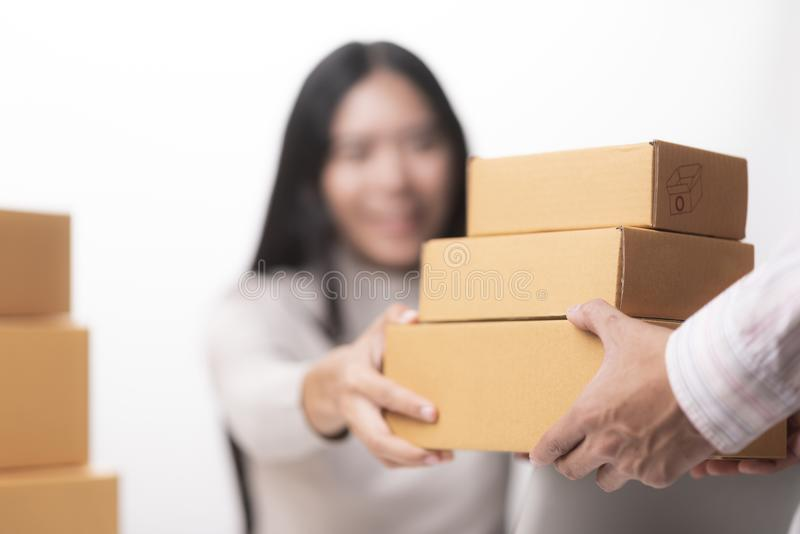 Happy businesswoman receiving a package sitting on a desk at off. Ice royalty free stock photos