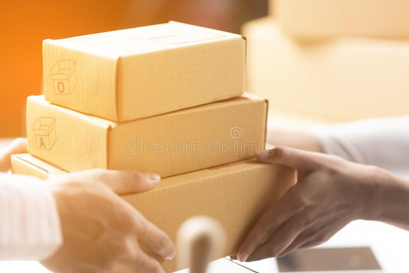Happy businesswoman receiving a package sitting on a desk at off. Ice royalty free stock image