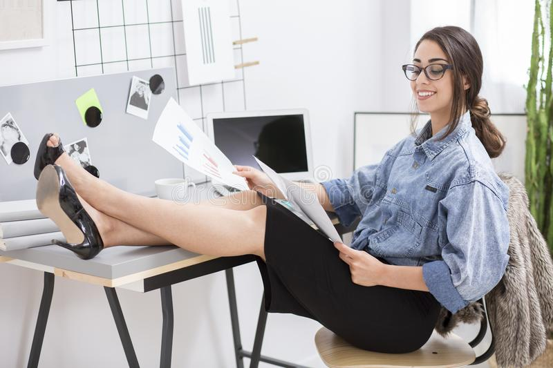 Happy businesswoman reviewing company reports royalty free stock photography