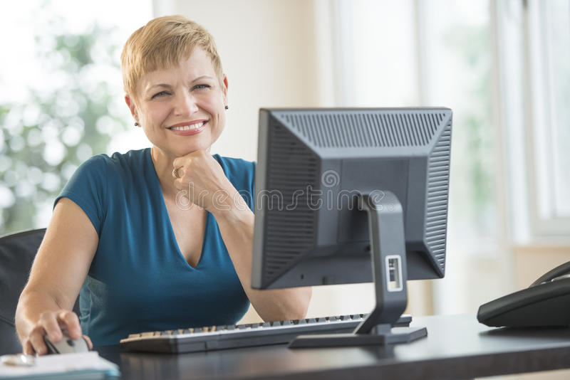 Happy Businesswoman Sitting At Computer Desk