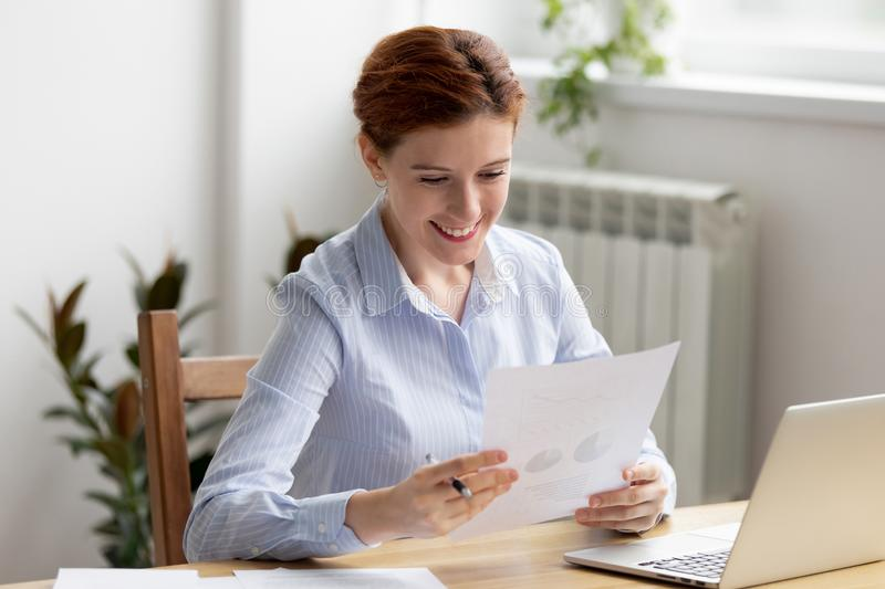 Executive female manager analyzing sales statistics chart. Happy businesswoman sitting at desk looking income chart shown on paper feels satisfied. Executive stock photo