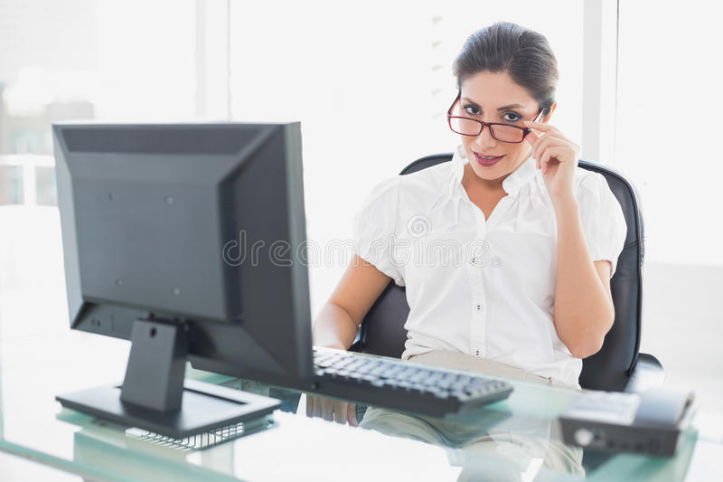 Happy Businesswoman Sitting At Her Desk Looking At Camera Royalty Free Stock Images