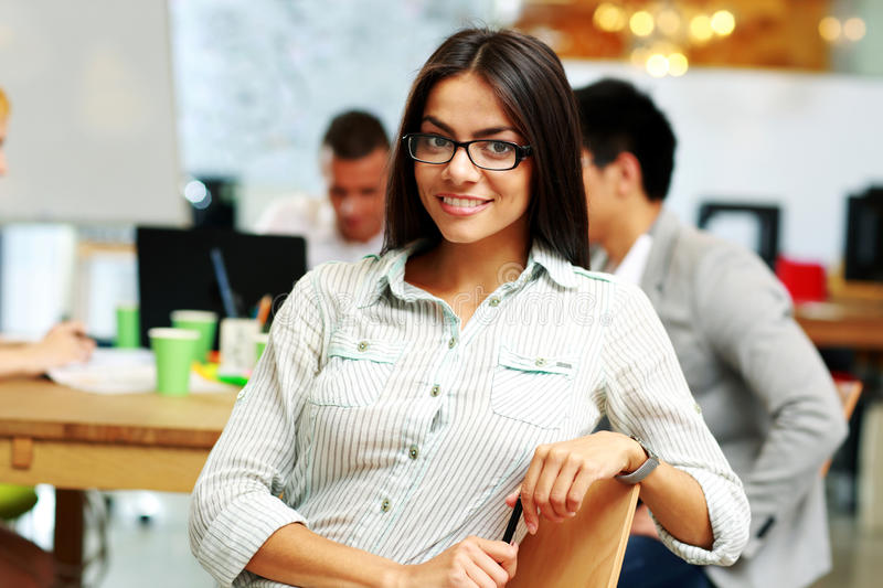 Happy businesswoman sitting in the office. In front of his colleagues royalty free stock photography