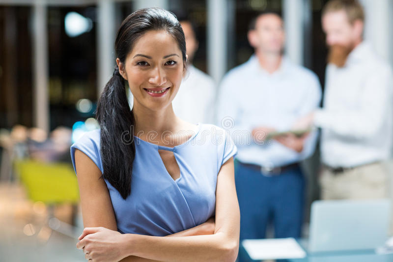 Happy businesswoman standing with arms crossed in the office stock images