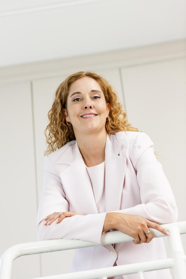 Happy businesswoman standing in hallway royalty free stock images
