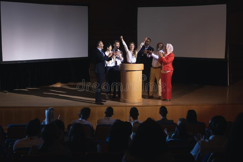 Happy businesswoman standing at the stage of the auditorium with colleagues stock photo