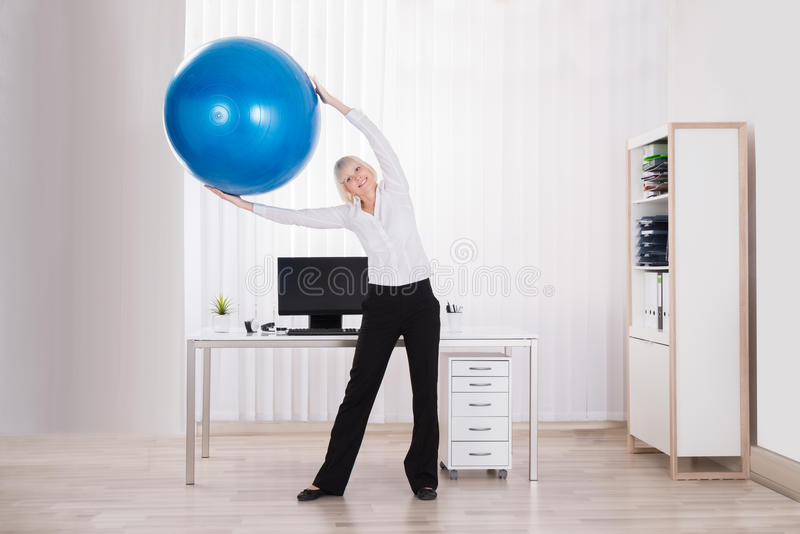 Businesswoman Stretching Her Arms In Office. Happy Businesswoman Stretching Her Arms Using Fitness Ball In Office royalty free stock images