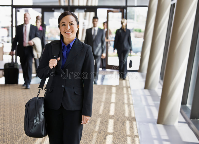 Happy businesswoman in suit holding briefcase stock photos