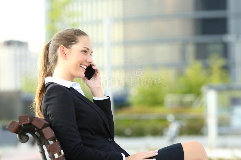Happy businesswoman talking on phone on a bench stock photos