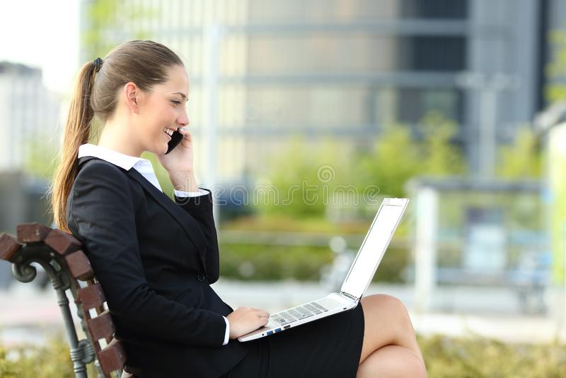 Happy businesswoman talking on phone checking laptop stock image